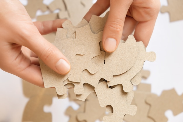 Cardboard puzzles in female hands, close up.