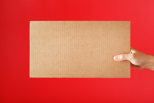 Cardboard sign in hand on a red surface with free space