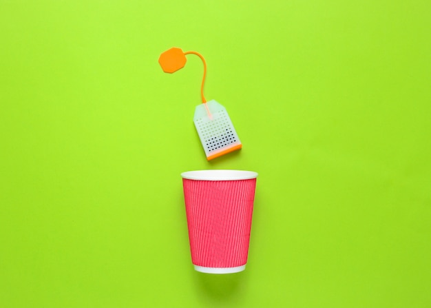 Cardboard tea cup and teabag on green background
