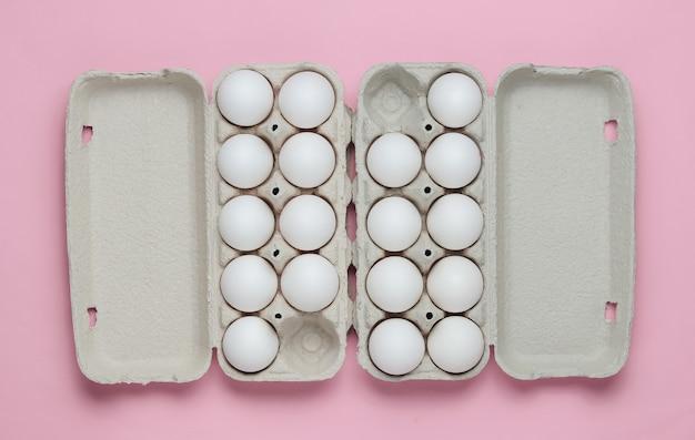 ピンクのパステルカラーの背景に卵と段ボールトレイミニマリズム料理のコンセプト