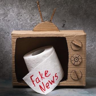 画面の偽のニュースの概念から突き出ているトイレットペーパーのロールと段ボールのテレビモデル