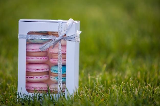 緑の草の芝生の背景にカラフルな手作りマカロンクッキーと段ボールの白いギフトボックス。