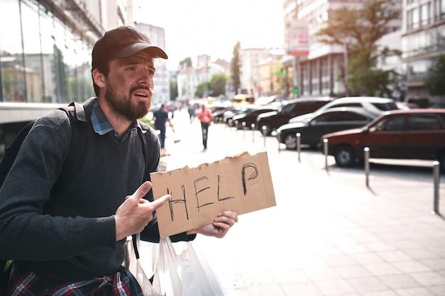 貧乏人は助けを言うcardbpardに手を差し伸べる