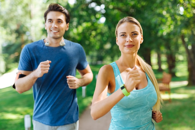 Cardio activity. delighted joyful couple smiling while jogging in the park together