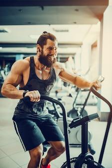 Молодой человек используя велотренажер на спортзале. мужчина фитнеса используя воздушный велосипед для cardio разминки на спортзале crossfit.