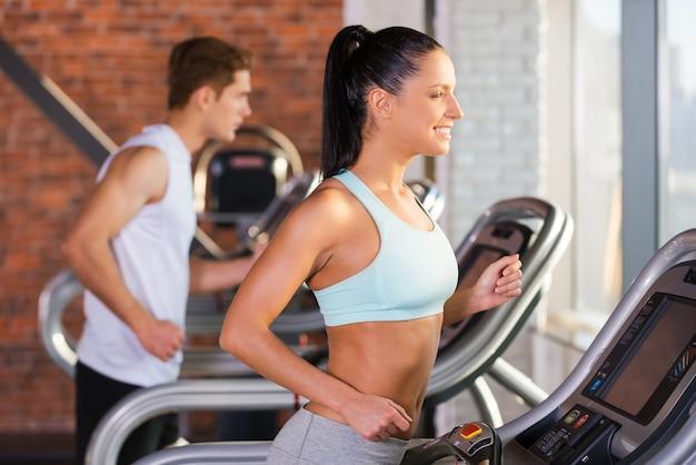 Кардио тренировки. вид сбоку красивой молодой женщины, бегущей на беговой дорожке и улыбающейся с мужчиной на заднем плане