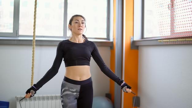 Кардио тренировки в тренажерном зале. молодая женщина, прыжки через скакалку