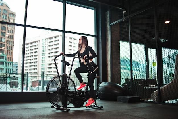 カーディオトレーニング。ジムでエアロバイクを使用して若いスポーティな女性。