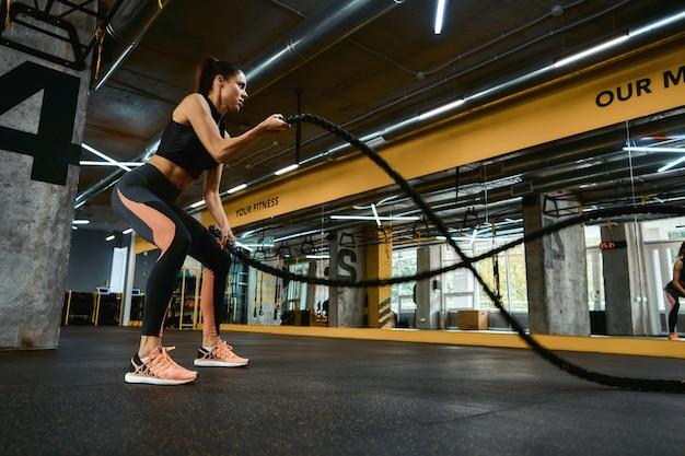 有酸素運動。クロスフィットジムでバトルロープを使って運動するスポーツ服を着た若い強い運動女性、全身。スポーツ、トレーニング、健康的なライフスタイル