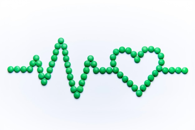 Cardiogram with heart from green pills on white background.