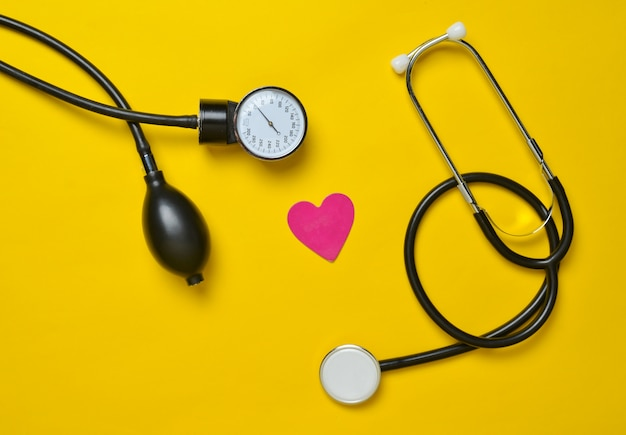 Cardiological concept. medical monometer, stethoscope, decorative heart on a yellow background. top view.