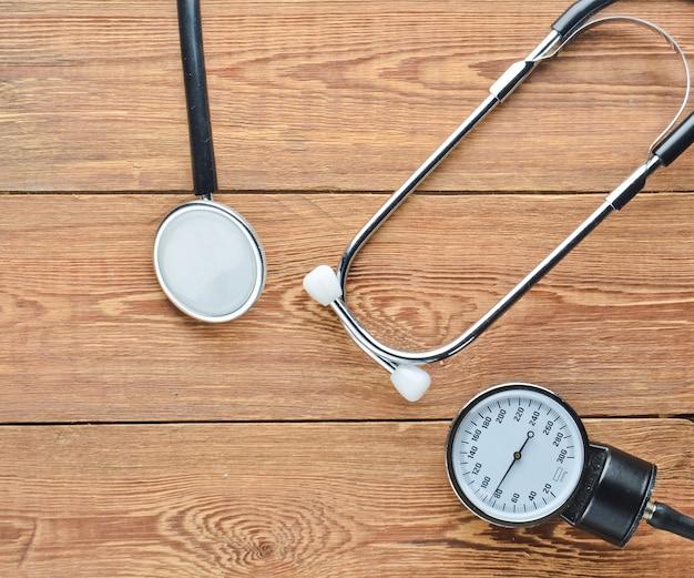 Кардиологическое медицинское оборудование для измерения давления на деревянном столе. стетоскоп и измерительный прибор. вид сверху.
