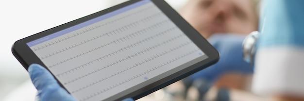 Кардиолог изучает электрокардиограмму пациента на планшете крупным планом