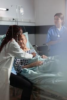 医療訪問中に年配の男性を検査する制服を着た心臓専門医