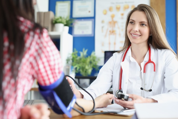 Cardiologist measuring woman blood pressure at clinic appointment