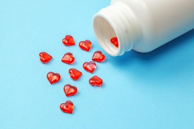 心臓病の丸薬。青い背景にボトルとハートの形をした赤い錠剤。