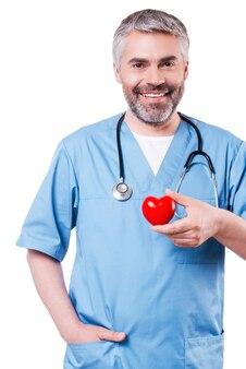 Кардиологический хирург. уверенный зрелый хирург-кардиолог держит игрушку в форме сердца и улыбается, стоя изолированным на белом
