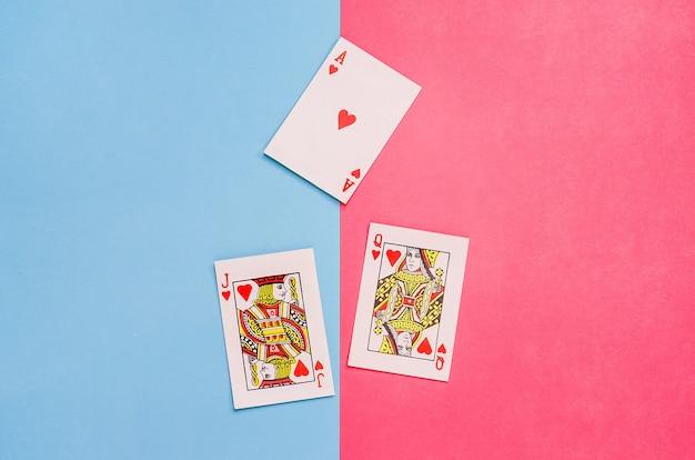 カード-ピンクとブルーの背景にエース、クイーン、ハートのジャック。男性と女性の関係、愛の概念。