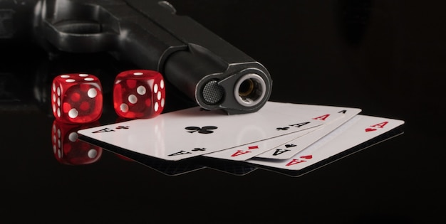 Cards dice and a gun on a black background gambling and entertainment casino and poker