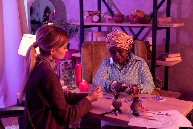カードの意味。カードの意味を説明する巨大なリングを身に着けているアフリカ系アメリカ人のふっくら占い師