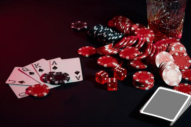 テーブルの上のポーカープレーヤーのカードは、チップとグラスのカクテルとウイスキーの組み合わせです...