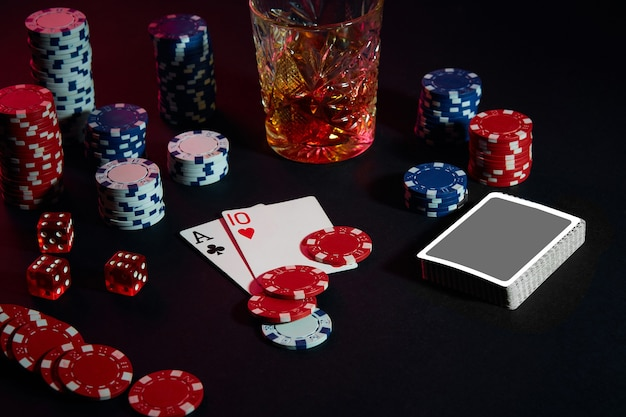 テーブルの上のポーカープレーヤーのカードは、カードのウィスキーの組み合わせとチップスとカクテルのグラスです