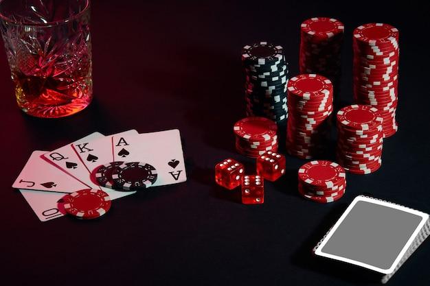 ポーカープレーヤーのカード。テーブルの上には、チップスとウイスキーのカクテルがあります。静物。ギャンブルの概念。ポーカーオンライン。カードの組み合わせ-ロイヤルフラッシュ