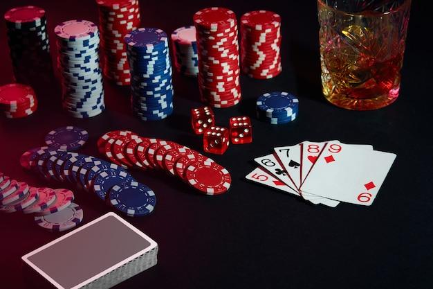 ポーカープレーヤーのカード。テーブルの上には、チップスとウイスキーのカクテルがあります。静物。ギャンブルの概念。ポーカーオンライン。カードの組み合わせ