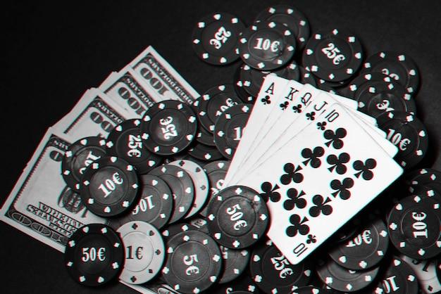 ポーカーのギャンブルゲームでチップとお金の山にロイヤルフラッシュが付いたカード。グリッチ効果のある白黒写真
