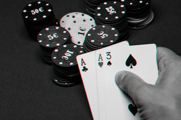 Cards with one pair of aces in the hands of a poker player in a casino on the table with chips. black and white photo with glitch effect