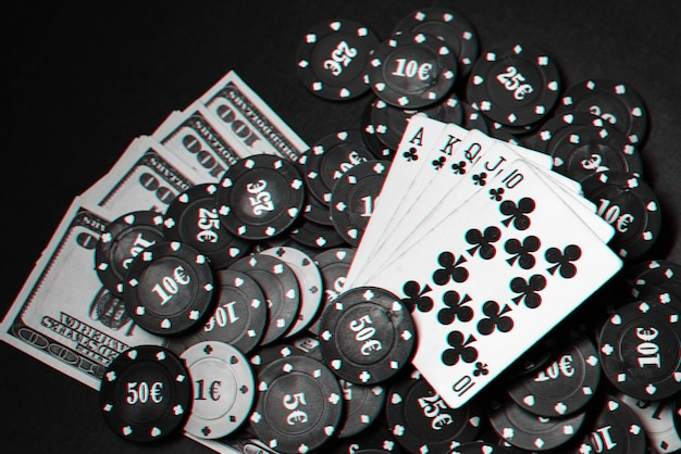 Cards with a royal flush on a pile of chips and money dollars in a gambling game of poker. black and white photo with glitch effect