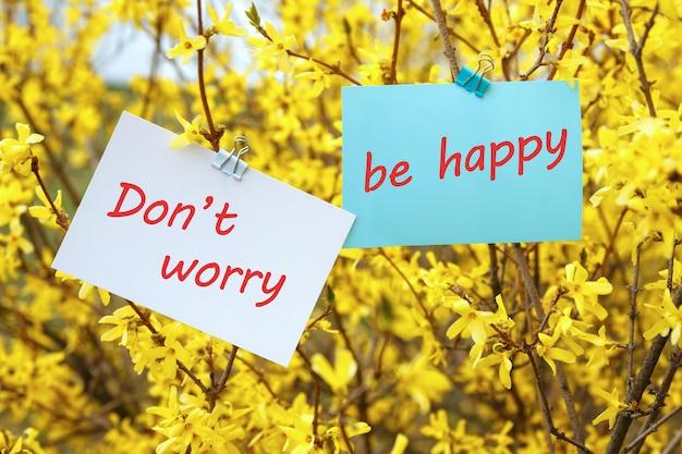 碑文のあるカード心配しないで、春の黄色い花のテーブルで幸せになってください。