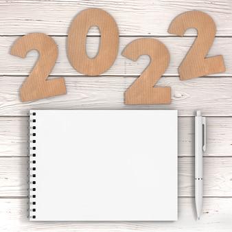 Cardstock numbers 2022 happy new year sign возле белой спиральной бумажной обложки ноутбука с ручкой на фоне деревянного стола. 3d рендеринг