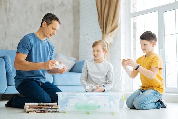 자연에 대한 관심. 쾌활한 십대 전 소년과 어린 아버지가 바닥에 앉아 플라스틱 병을 부수고 용기에 넣고 재활용 준비를합니다.