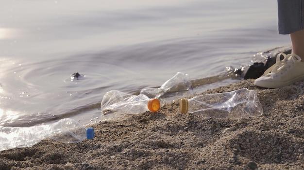 Заботьтесь о природе. девушка-волонтер собирает мусор в мусорный мешок. концепция планеты без мусора. очистка природы, добровольная экология зеленая концепция. загрязнение окружающей среды пластиком.
