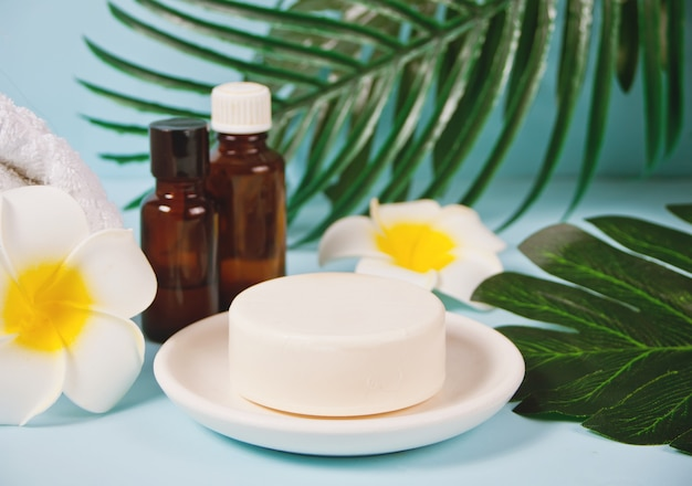 Care, beauty and spa concept. organic soap and small bottles with essential oils under a palm leaf.
