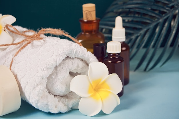 Care, beauty and spa concept. organic soap, small bottles with essential oils, white towel, palm leaf, plumeria frangipani flower.