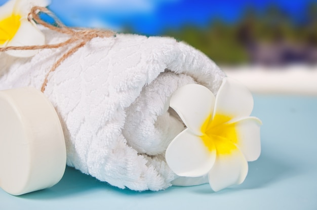 Care, beauty and spa concept. organic soap, white towel, plumeria frangipani flower. ocean coastline on the table.