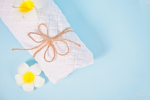 Care, beauty and spa concept. white towel and plumeria frangipani flower. copy space. top view.