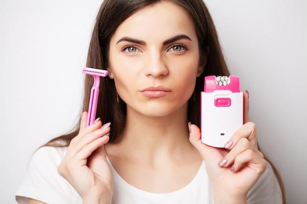 Концепция ухода, женщина, держащая эпилятор и бритву возле лица, чтобы удалить волосы