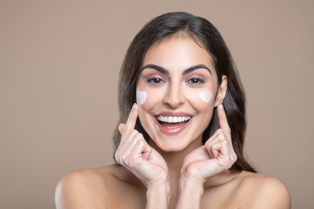 Care cosmetics. happy pretty woman with brown eyes and bare shoulders pointing fingers at cream on her cheeks