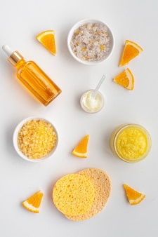 Care cosmetics with vitamin c. mask, cream, serum and bath salt with orange oil and vitamin c. flat lay. nop view.