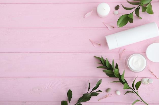 色付きの背景にケアクリームと花トップビュースキンケア化粧品