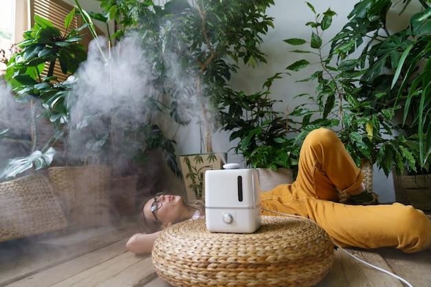 습도와 실내 식물 건강 개념을 유지하기 위해 집에서 가습기를 사용하여 관엽식물을 돌보세요