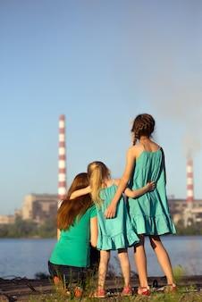ケアの未来のコンセプト。姉妹は空気を汚染している煙突の茎を見ています