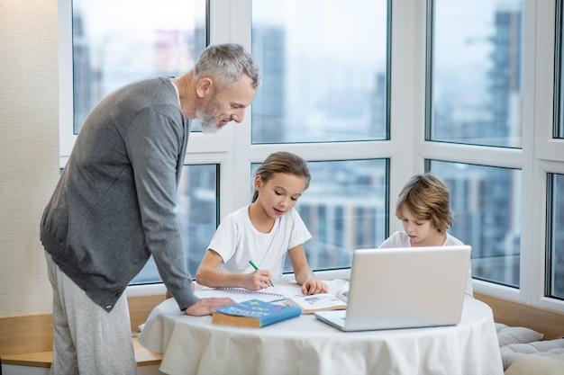 케어, 도와주세요. 노트북에 앉아 독서를 하고 성인을 돌보는 아빠를 돕는 집중된 초등학교 아이들