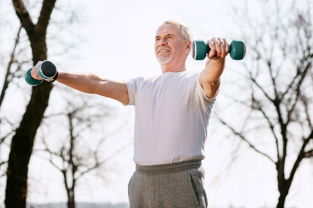 Заботься о себе. низкий угол привлекательного зрелого мужчины, тренирующегося с гантелями и позирующего в парке