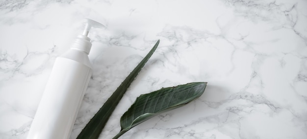 Care product and natural leaves on a marble surface