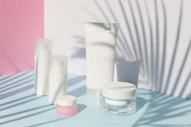 Care products set with palm leaf shadow. summer body care beauty treatment