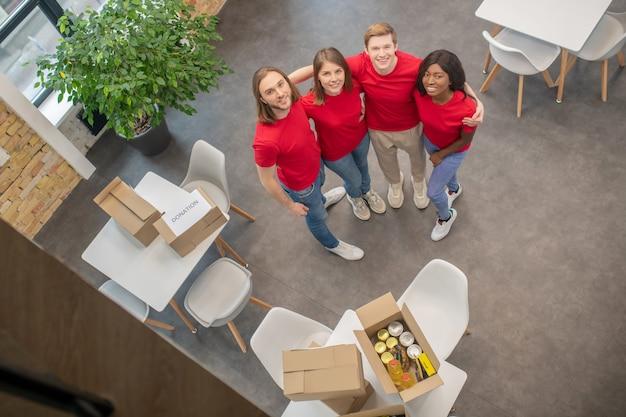 케어. 젊은 행복 학생 자원 봉사자의 팀은 도움을 위해 제품 상자와 함께 방에 포용 서